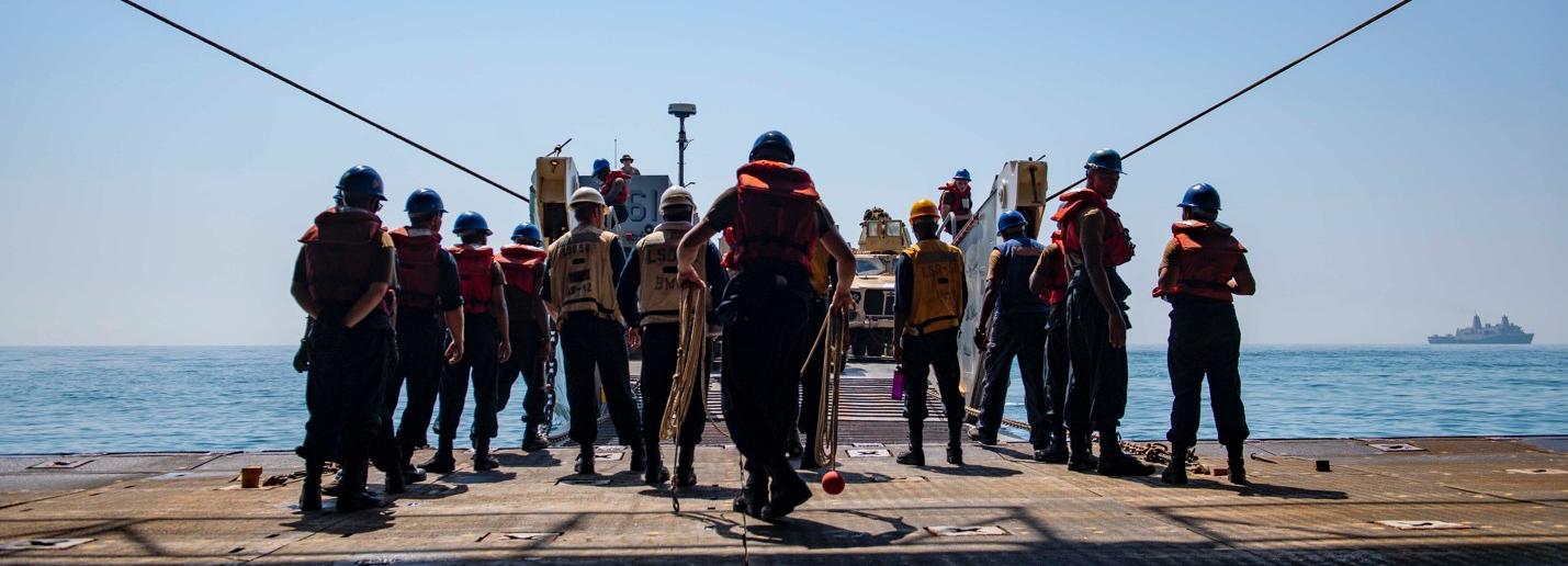 Sailors and Marines load vehicles onto Landing Craft, Utility (LCU)