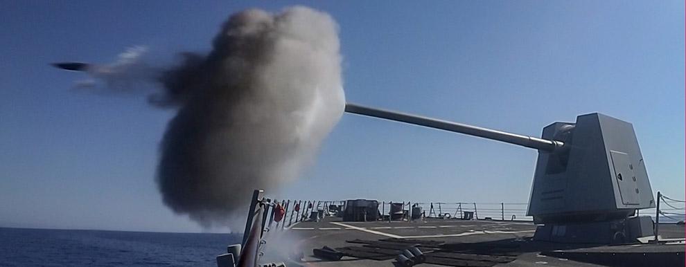 USS Jason Dunham (DDG 109) fires its Mark 45 5-inch gun.
